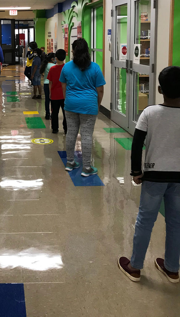 Students in a line, 6 squares apart, preparing for recess
