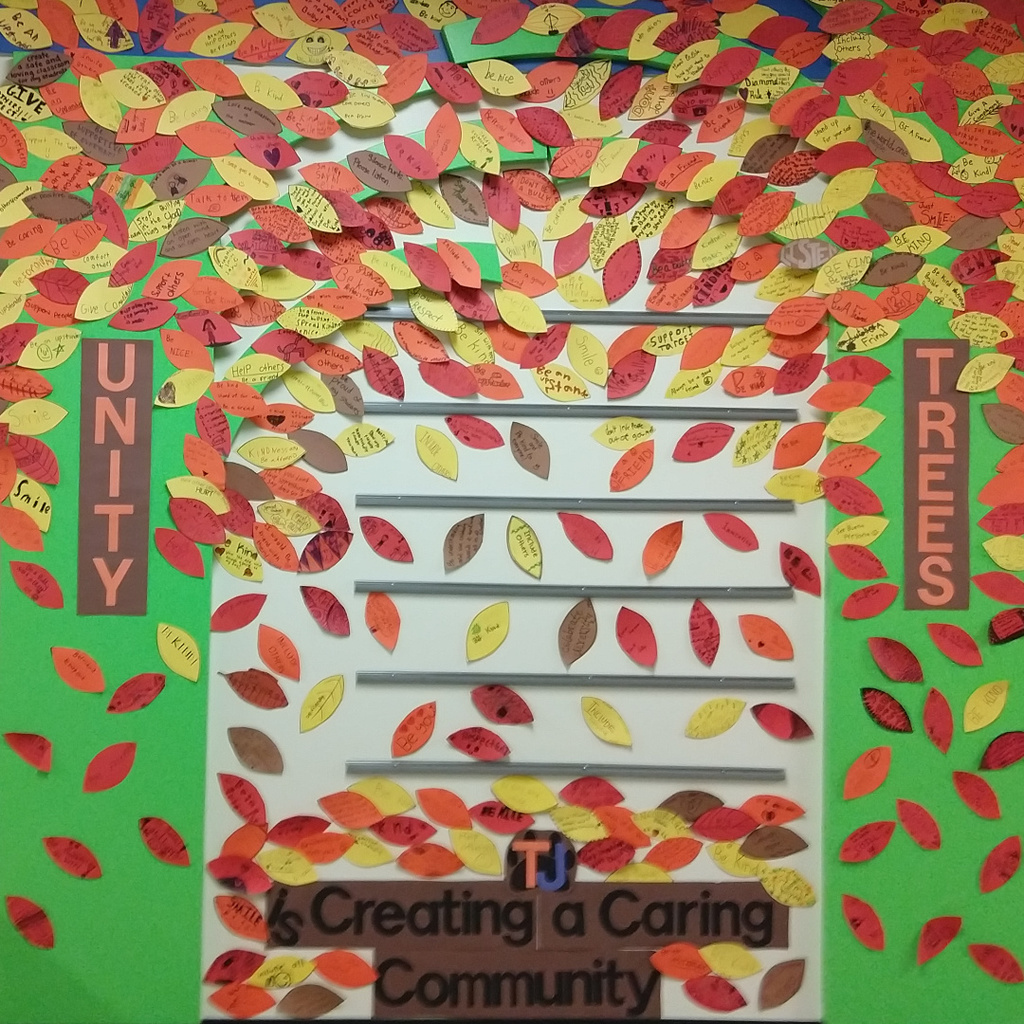 "Red, Orange, Yellow and Brown leaves with ways to be an ""Upstander"" adorn the hallway trees in honor of Unity Week"