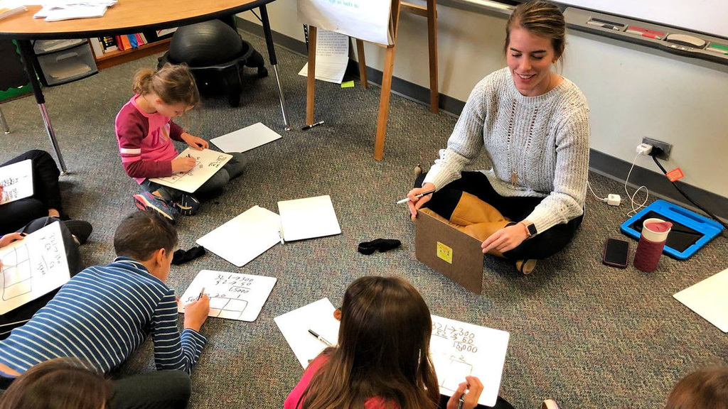 4th grade teacher surrounded by students with whiteboards learning math techniques
