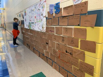 "Student adding a brown construction paper ""brick"" to the great wall of China knowledge outside the classroom door"