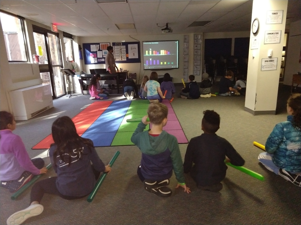 fifth grade students use boomwhackers and follow the notes on the smartboard to make beautiful music
