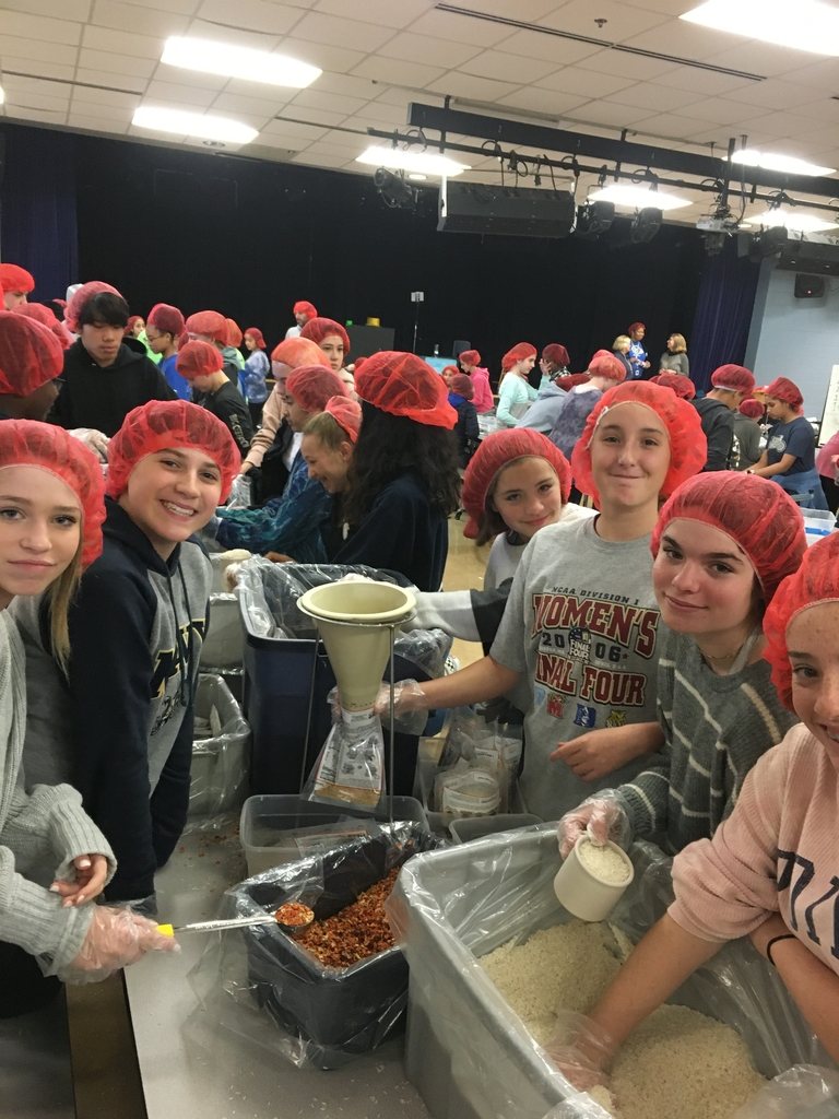 8th grade students pack meals. Teamwork is key!