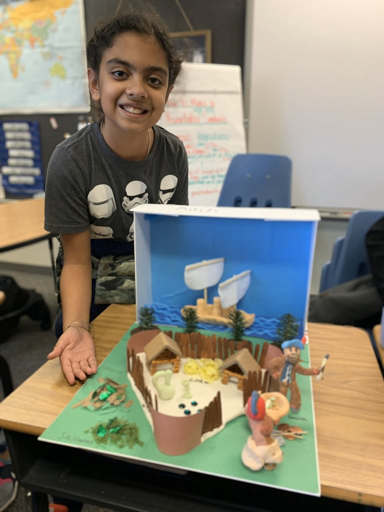 Student with Jamestown diorama - a triangular fort with buildings and a ship in the background