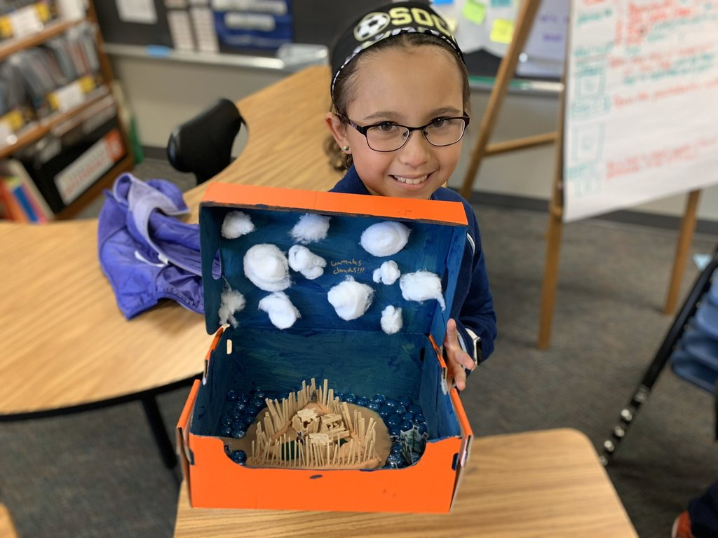 Student with Jamestown diorama - a triangular fort, a cloudy sky, and a beautiful blue ocean (and an organge box.  Go TJ!)