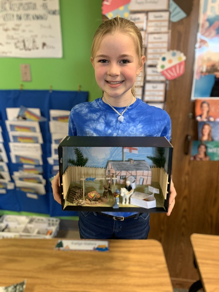 Student with Jamestown diorama - a fort with a building, characters cooking and drying hides over a fire.