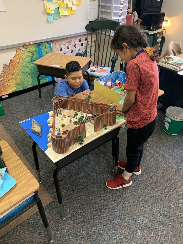 Student with Jamestown diorama - a triangular fort with trees, sentinels, blacksmiths and cooking over a fire