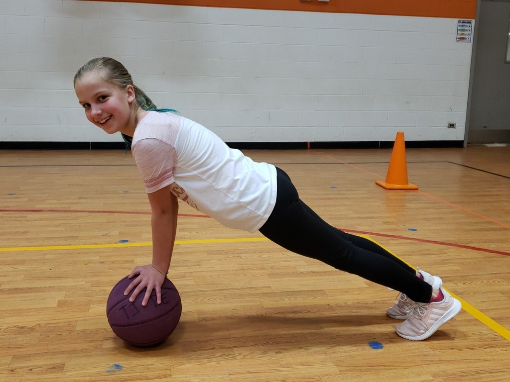 PE Student doing a plank on a basketball.  That takes plenty of core strength!