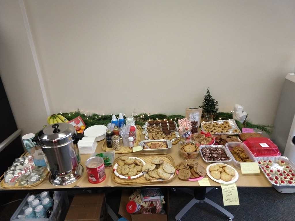 Table full of goodies:. tea, coffee, hit chocolate and cookies galore